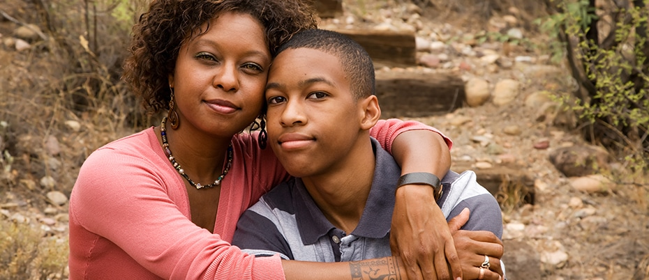 African American mom with arms around teenage son