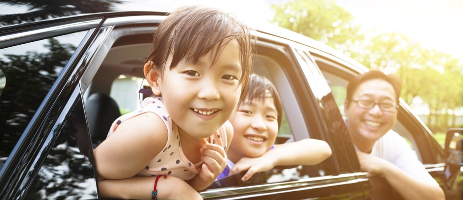 Family of three smile, leaning out of car