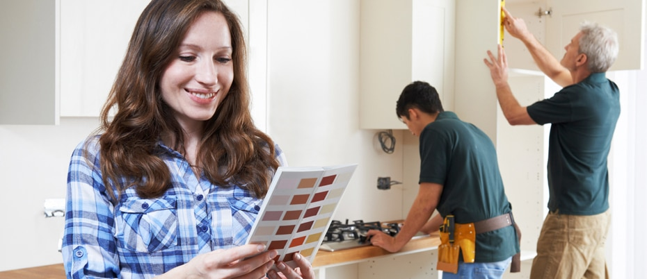 Smiling woman looks at paint chips with workers in background