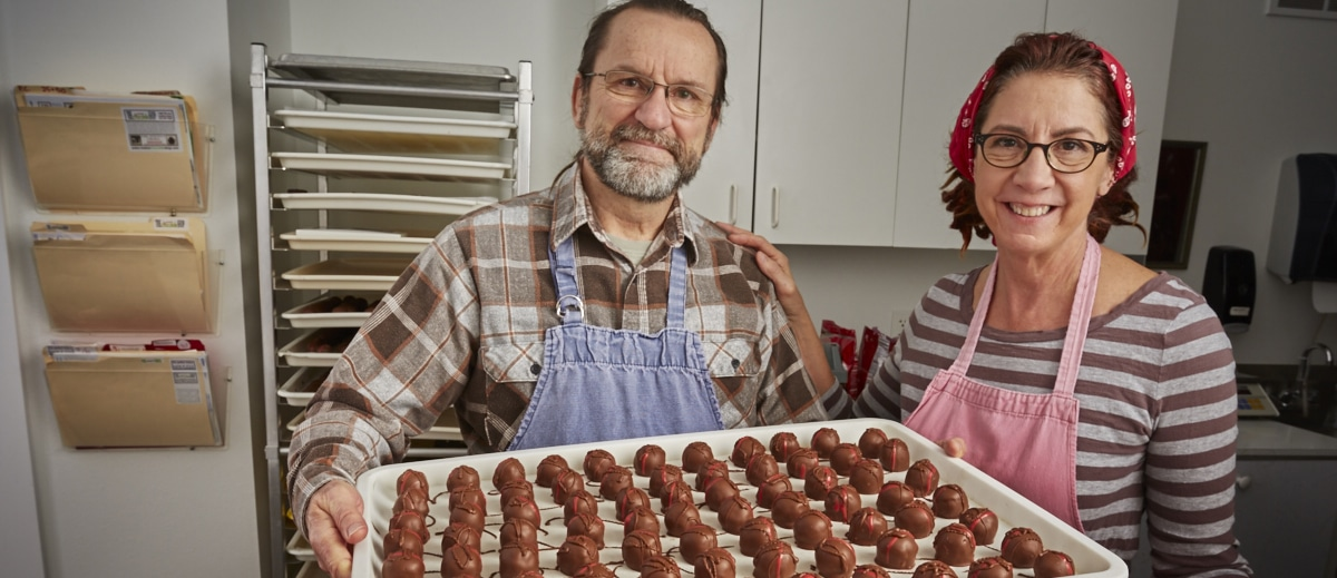 Male and female candymakers with tray of chocolates