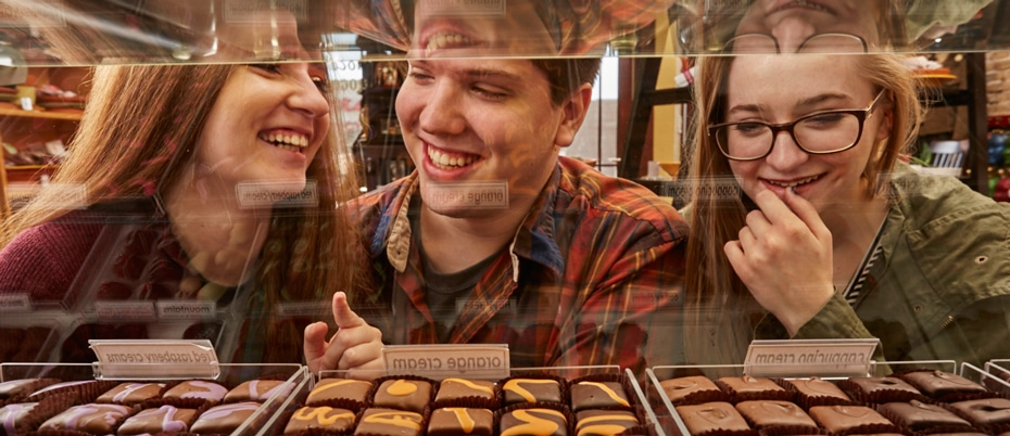 Three millennials choosing chocolates from inside a display case