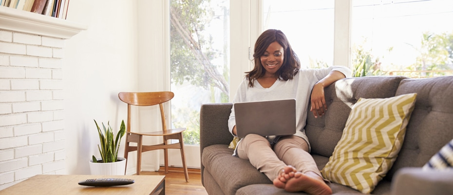 Woman Relaxing On Sofa At Home Using Laptop
