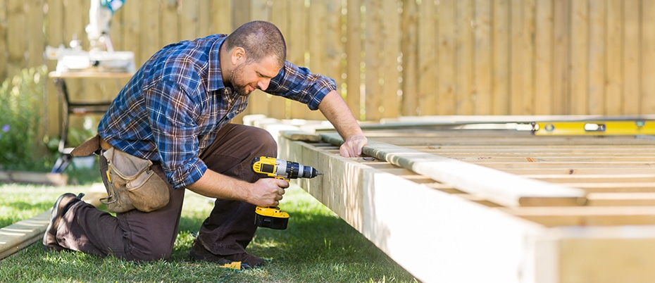 Man using drill to build new deck