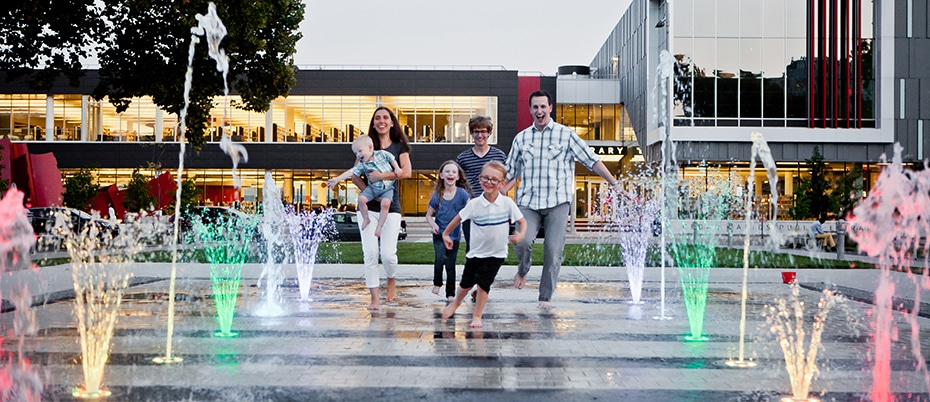 Family splashes in fountains in front of library