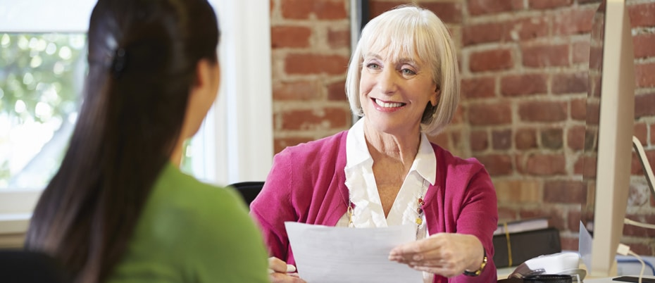 Smiling woman helping another woman with tax preparation