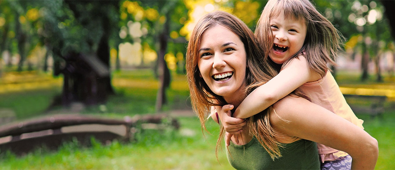 Mom giving piggyback ride to daughter in park