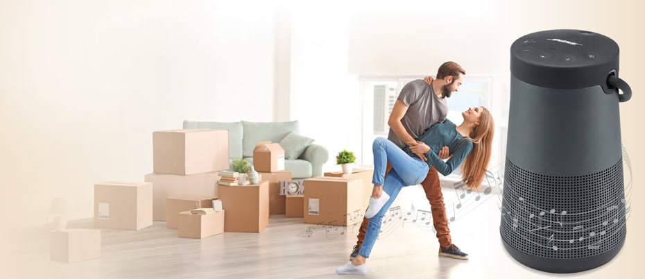 Man and woman dancing to music coming from a Bose speaker with moving boxes nearby