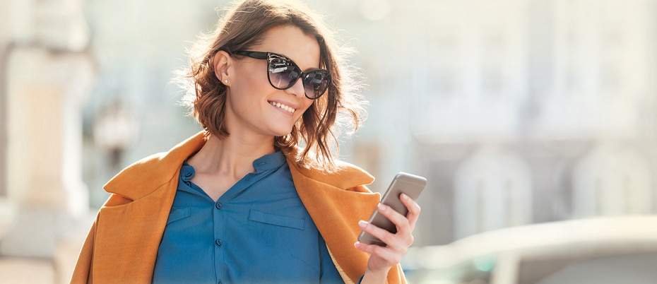 Woman in orange coat looking at mobile phone