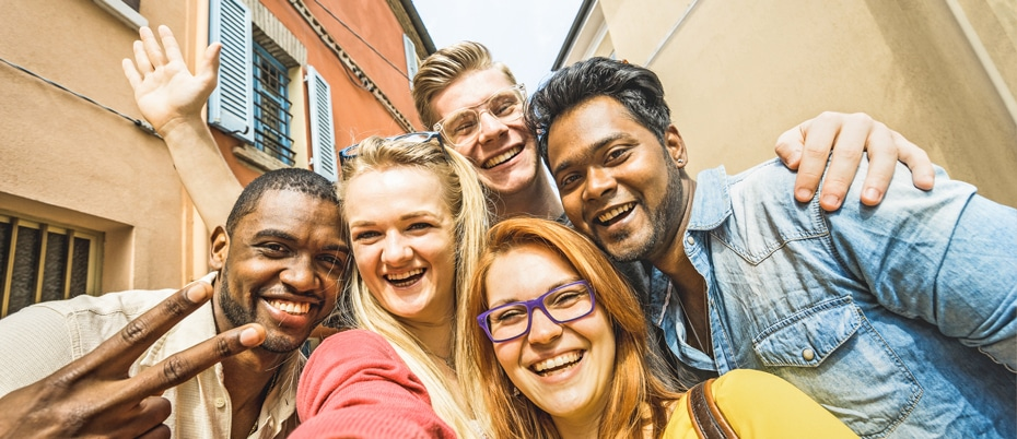 Group of happy young adults posing for selfie