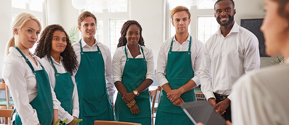 Employees wearing green aprons standing in a group, listening to their manager