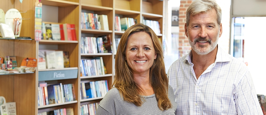 Bookstore owners standing in front of their bookshelves