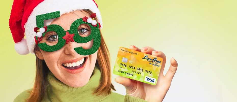 Woman wearing festive glasses holding credit card