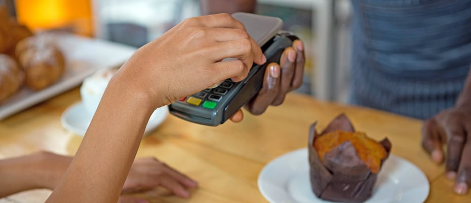 Mobile phone positioed above POS terminal to make payment using digital wallet. Muffin on counter in background
