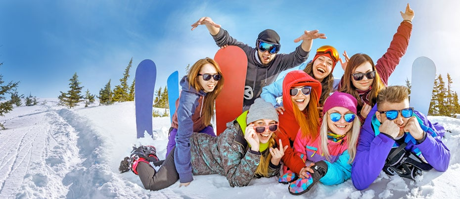 Friends with snowboards piled up in the snow mugging for a photo