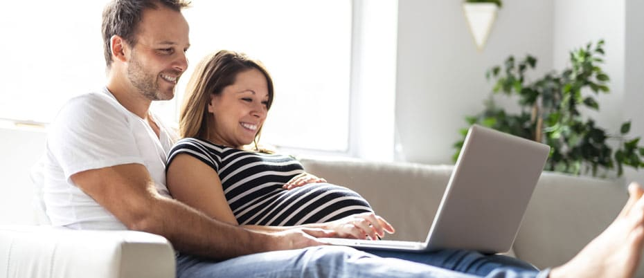 Pregnant couple on sofa using laptop computer