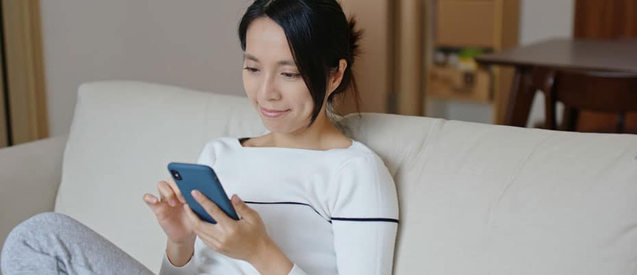 Woman sitting on her couch using her mobile phone