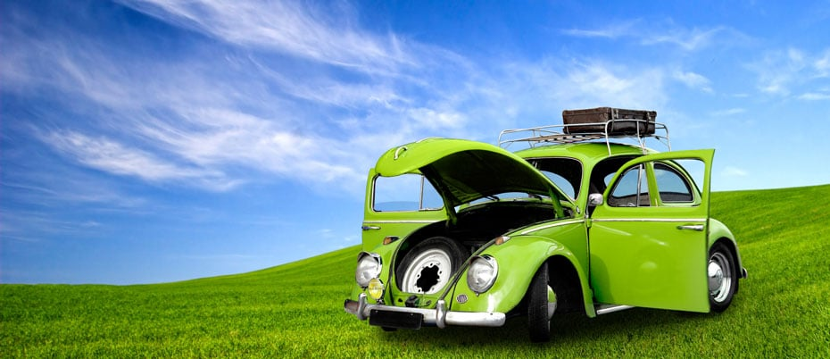 Lime green VW bug with hood open on rolling hill with blue sky
