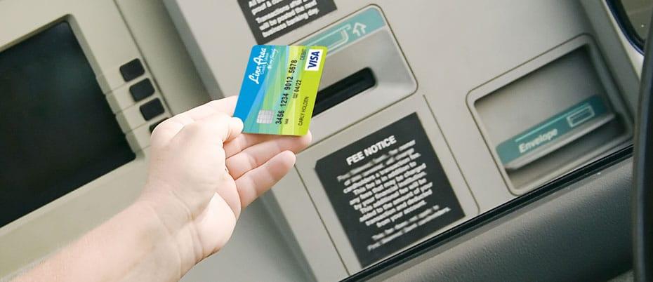 Person's hand holding a Linn Area card near an ATM