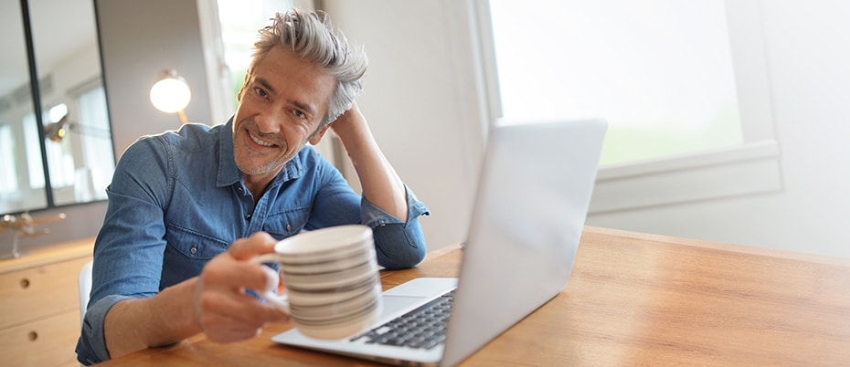 Mature man using laptop, smiling and raising a coffee cup toward the camera