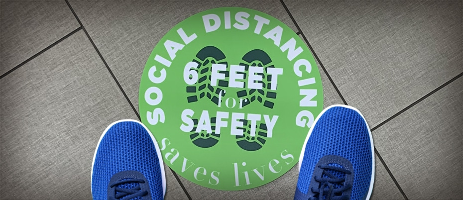 Blue shoes standing on a social distancing floor decal
