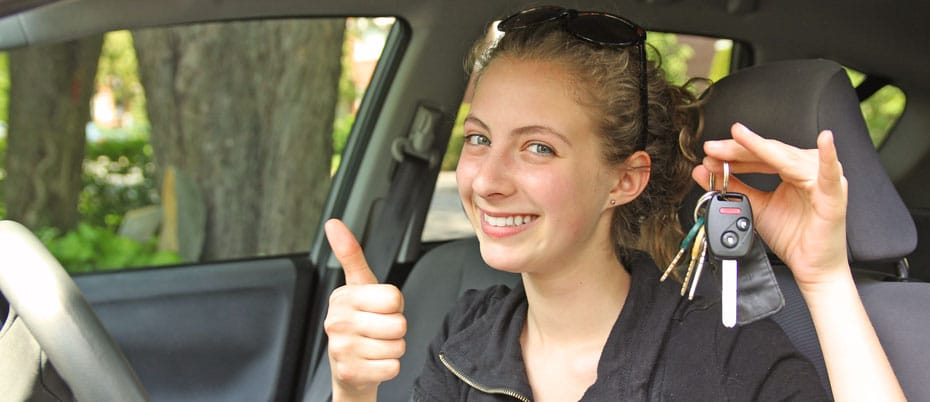 Young woman in car holding keys and flashing a thumbs up