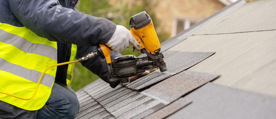 Construction worker using nail gun on shingles