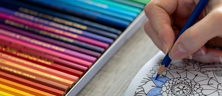 A hand coloring in a design with more colored pencils set aside in a tray