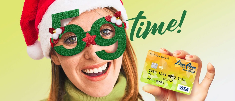 Woman wearing Santa hat and festive 5.9 glasses holding credit card