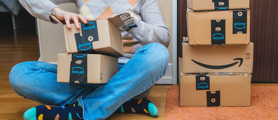 Person sitting on floor with several packages nearby